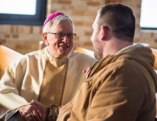 Bishop shakes hands with a male parishoner