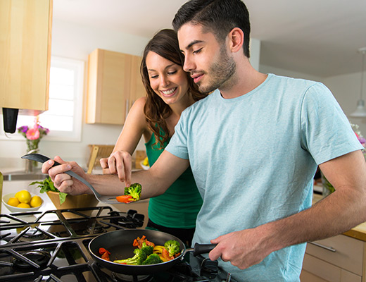 young adult male and female cook vegetables together on the stove