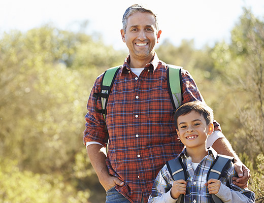 adult male and male child outdoors with backpacks on
