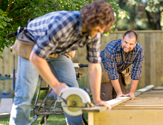 two men work together building a wooden structure