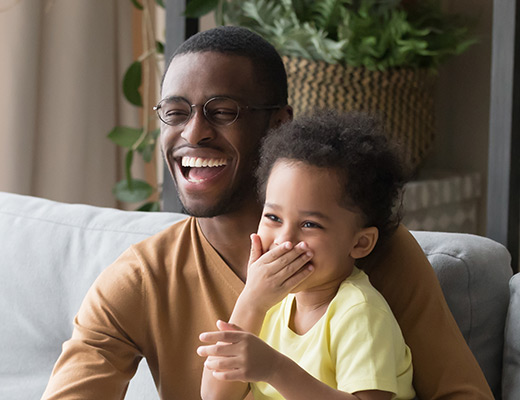an adult male and child laughing together while sitting on a couch