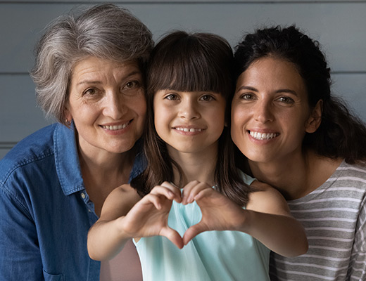 three generations of women smiling together while the little girl makes a heart shape with her hands