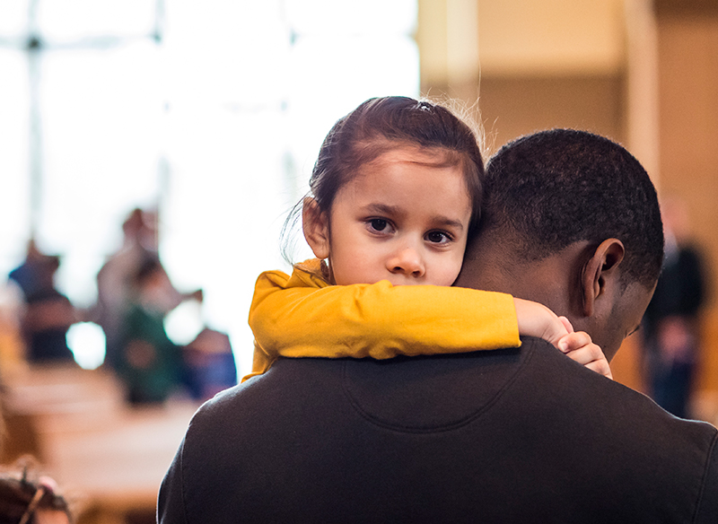 man holding young girl during a mass